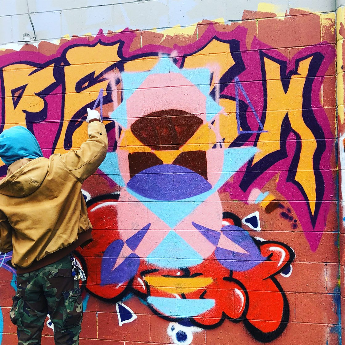 A young person using a spray paint can on a colorful mural