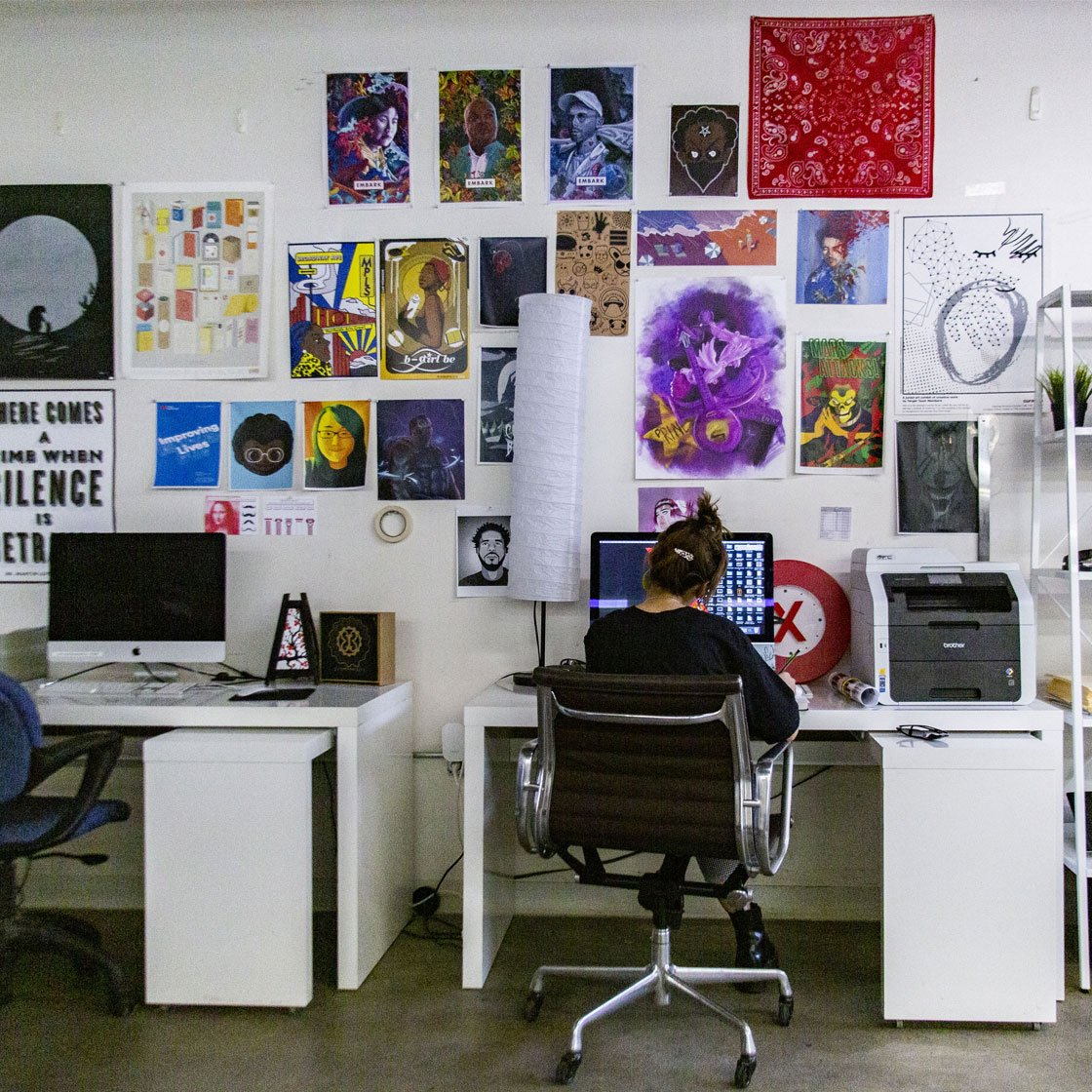 Someone sitting at a computer in front of a wall filled with different kinds of art and posters
