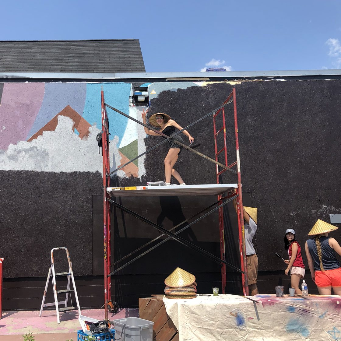 Several people painting a wall with a painting in progress. Some are standing on scaffolding.