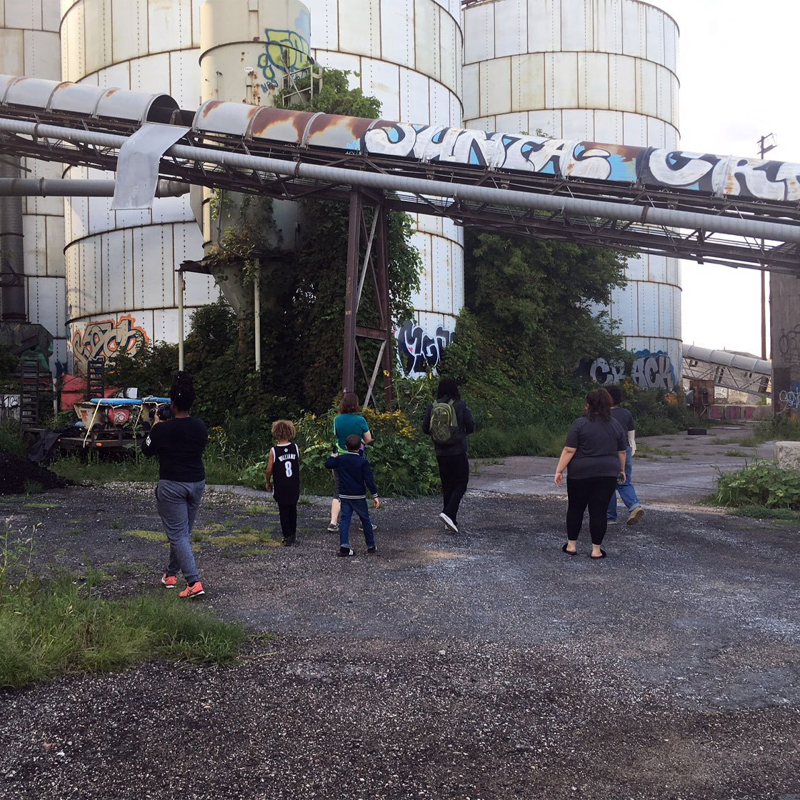 A group of people walking around an industrial area