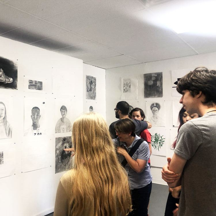 A group of people standing and admiring a wall of pencil drawn artwork