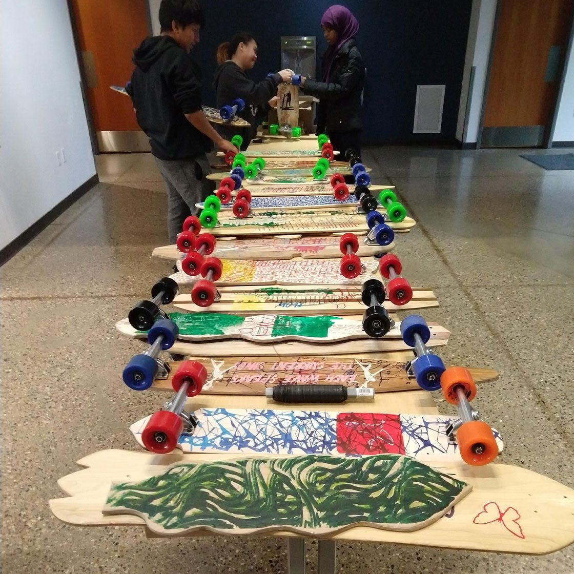 Decorative longboards displayed on a table with students working on them.