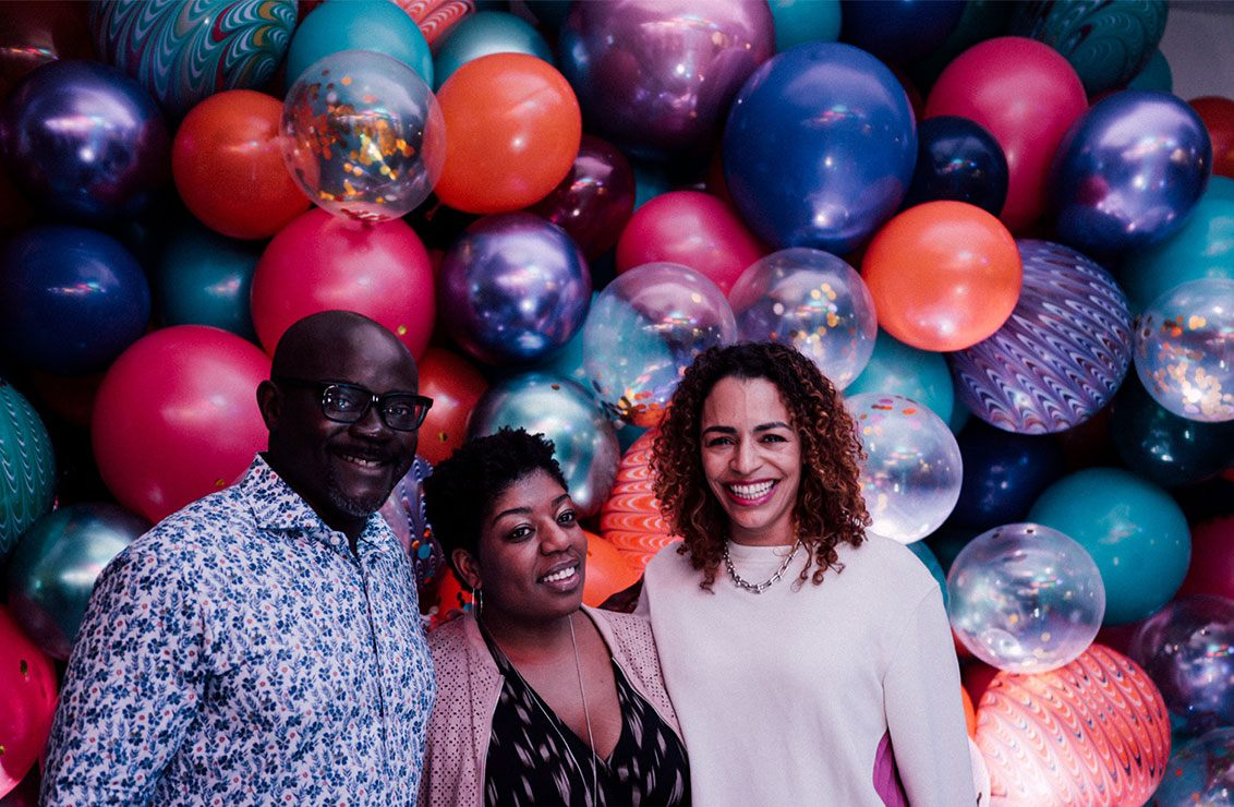 3 people posing in front of a highly colorful and decorative balloon wall