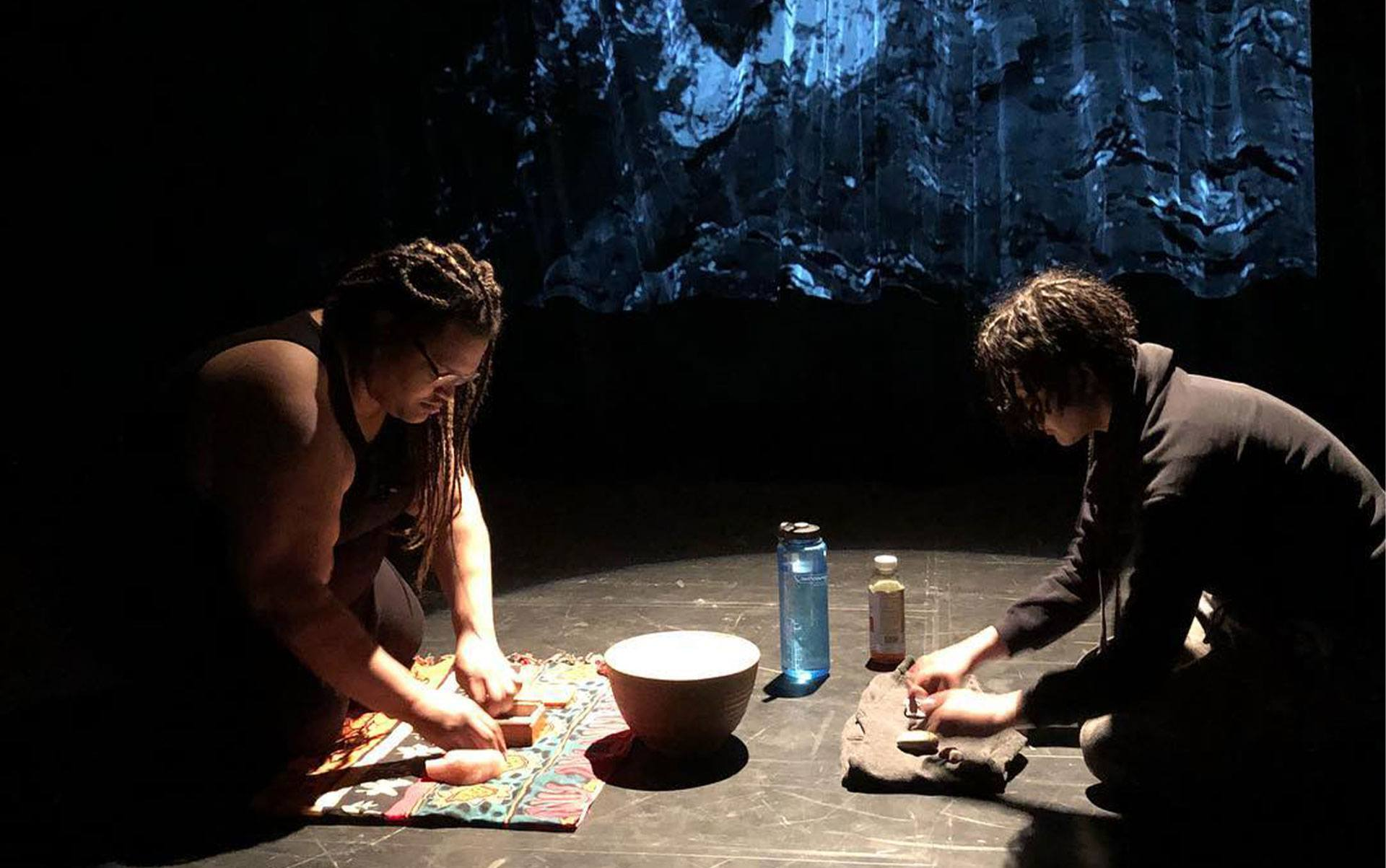 2 people sit working on different objects with their hands in a performance on a stage