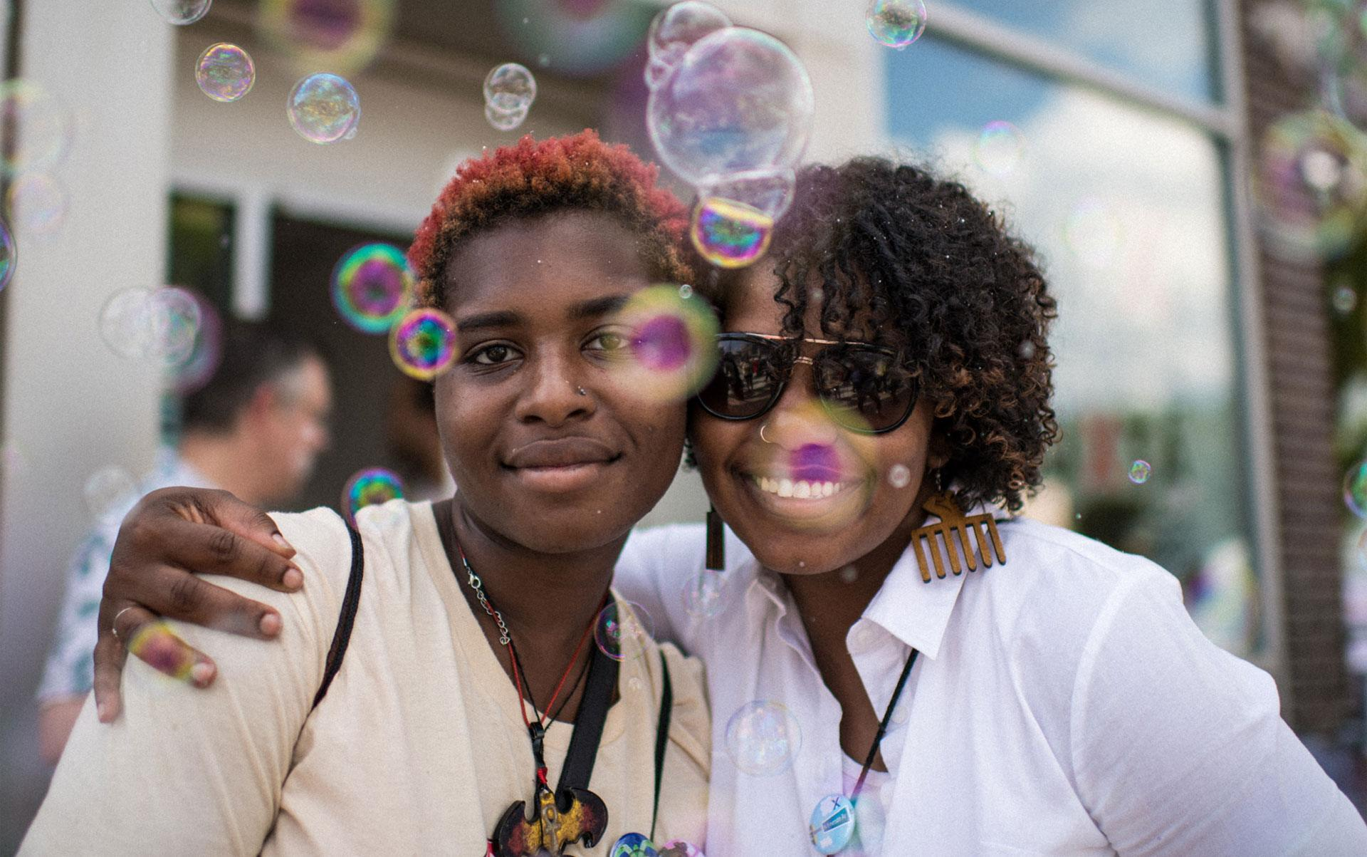 Two people embrace and smile directly at the camera. Bubbles are floating around them.