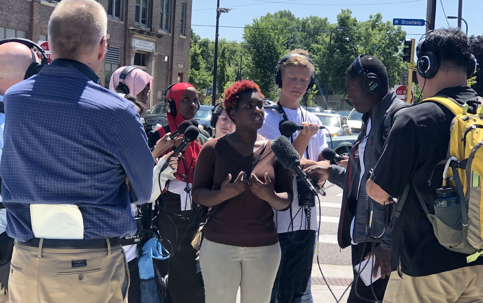Someone stands surrounded by reporters wearing equipment like headphones and microphones. The center person is speaking into the microphones.