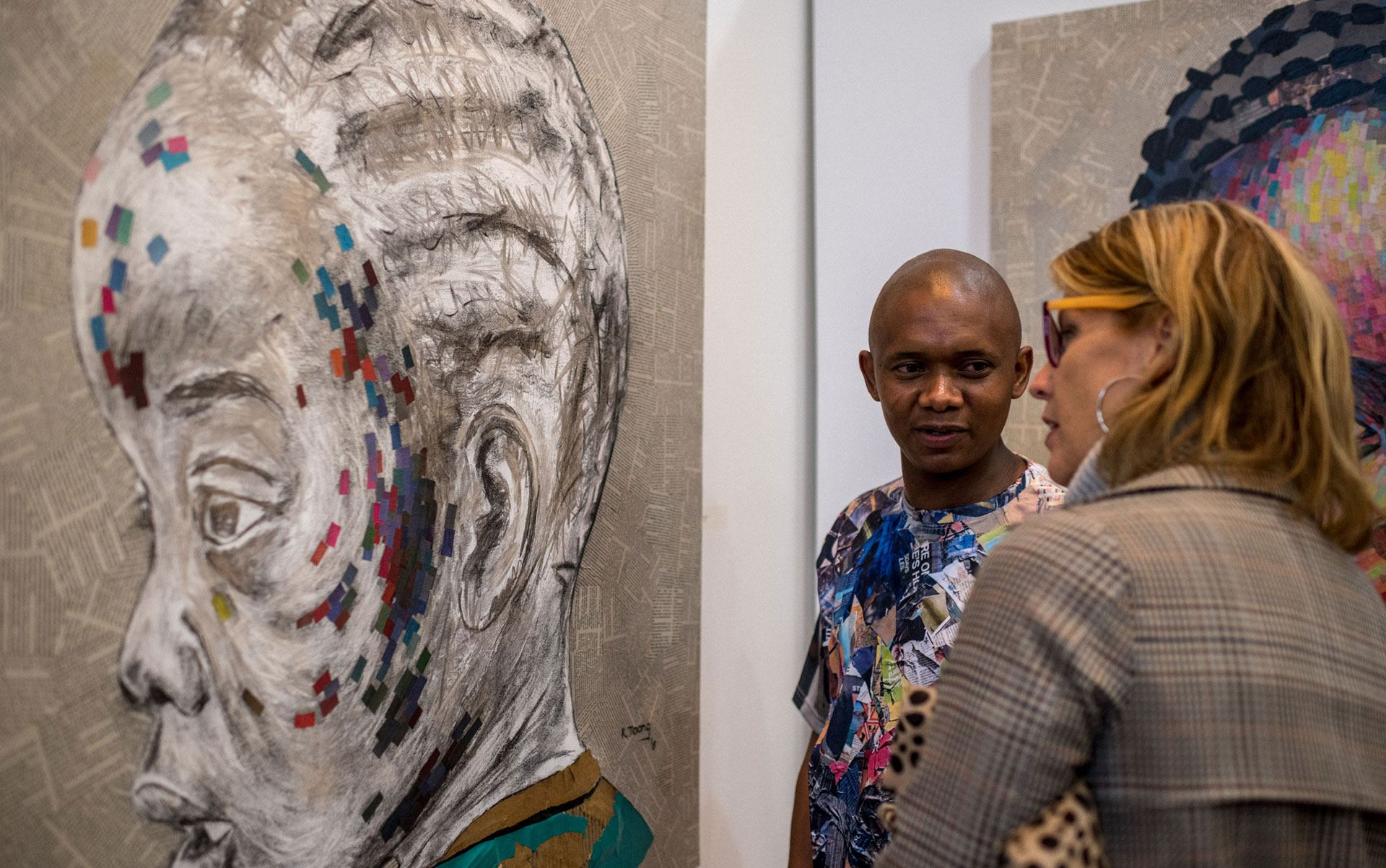 Two people stand in front of a painting and talk to each other.