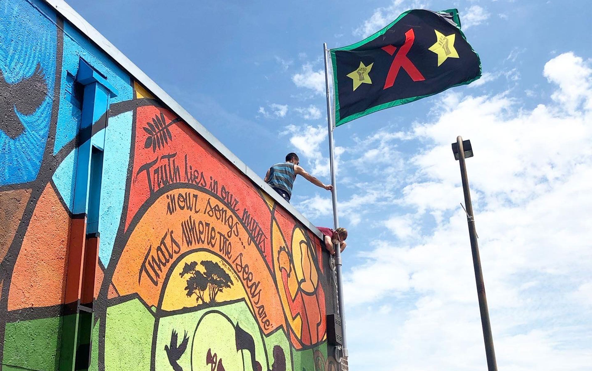 A wave with an X and two stars with raised fists in them waving against a blue sky and clouds atop a building with a colorful mural on the wall.