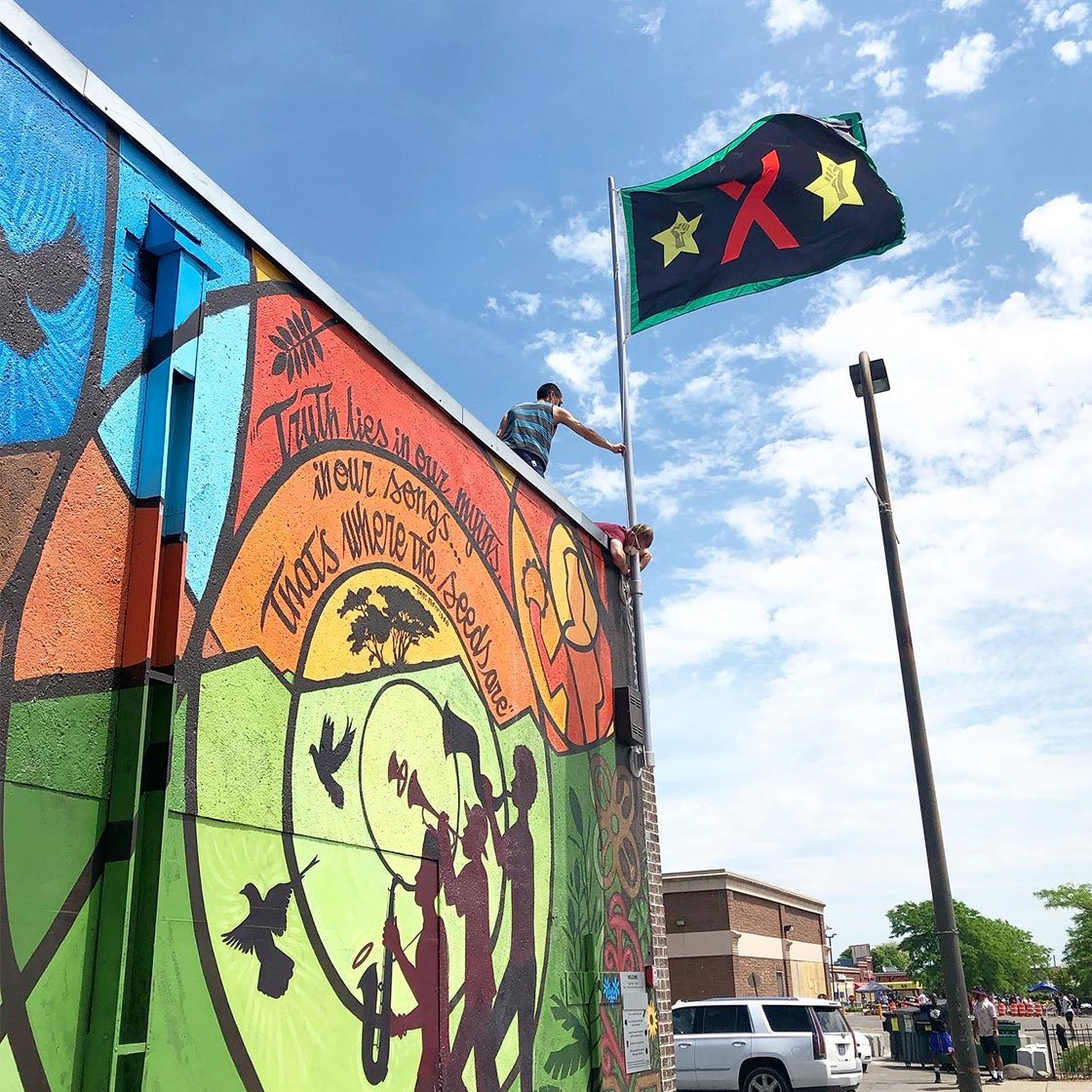 A colorful mural on the side of a building with a flag being raised from the roof