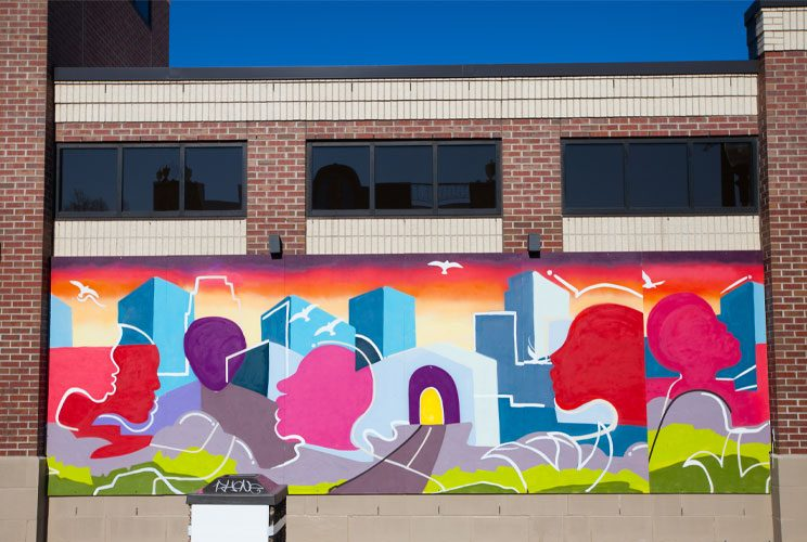 A mural painted with acrylic and spray paints depicting faces and buildings intermingling to represent the city of Minneapolis working together in unity.
