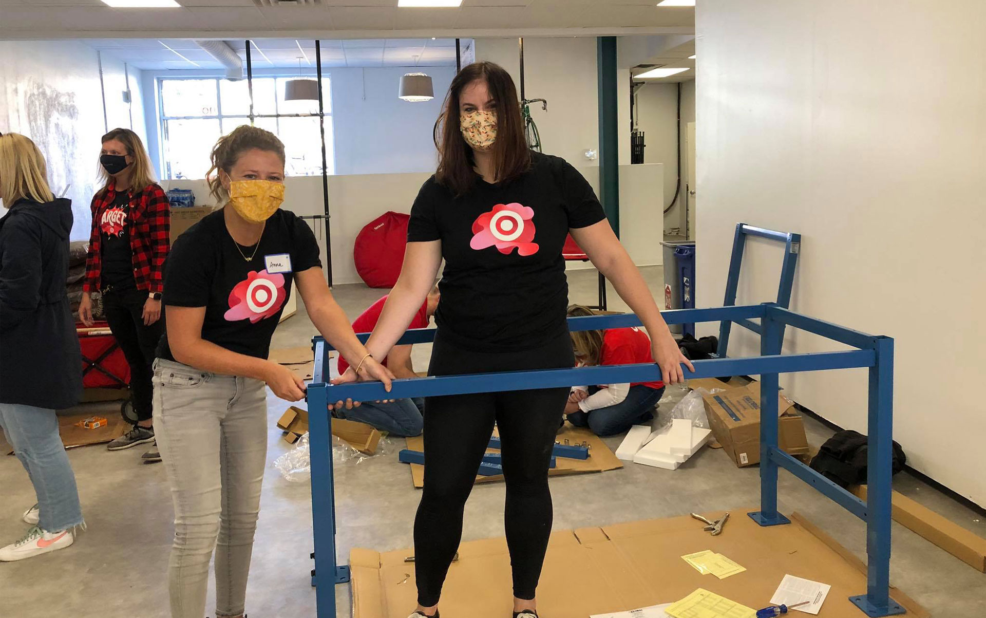 Two people, wearing masks, working together to build a table, posing for a picture