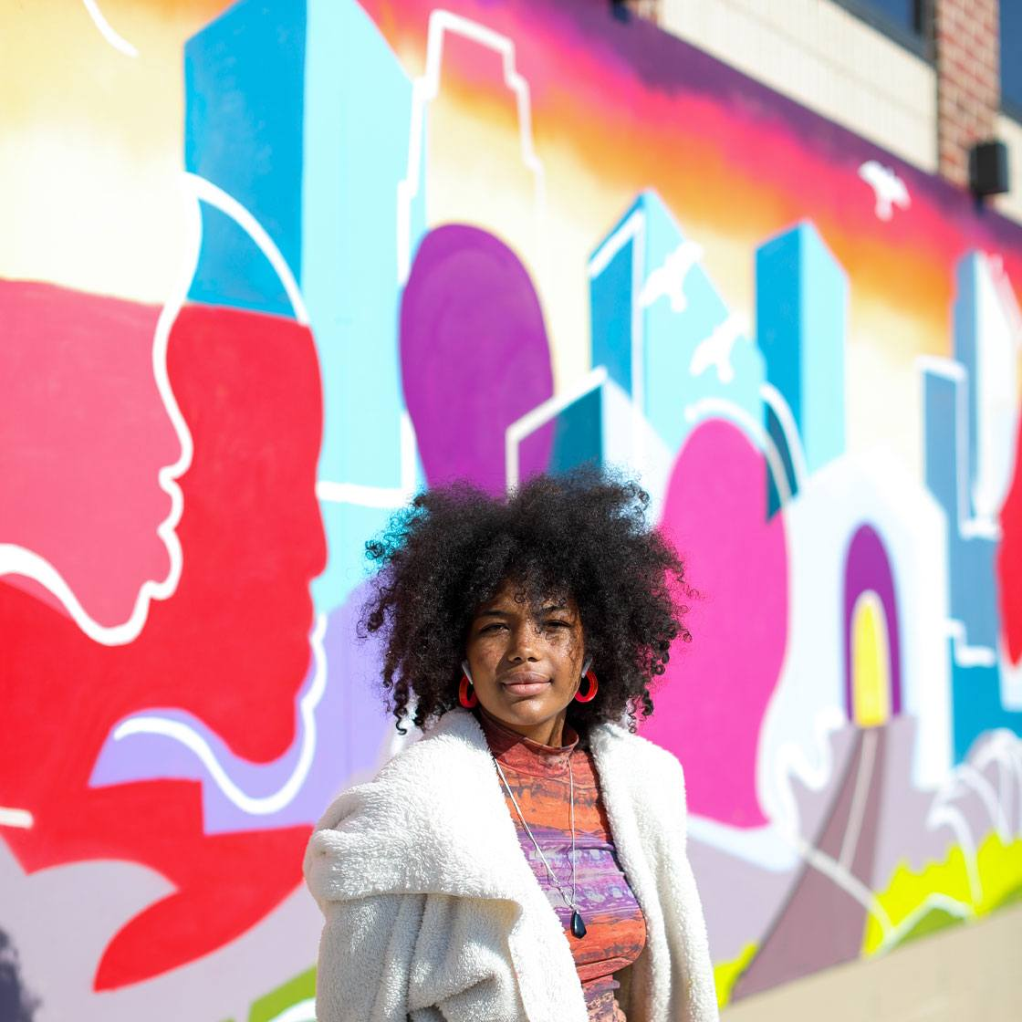 A mural painted with acrylic and spray paints depicting faces and buildings intermingling to represent the city of Minneapolis working together in unity. Apprentice Bereket Weddall poses in front of the mural.