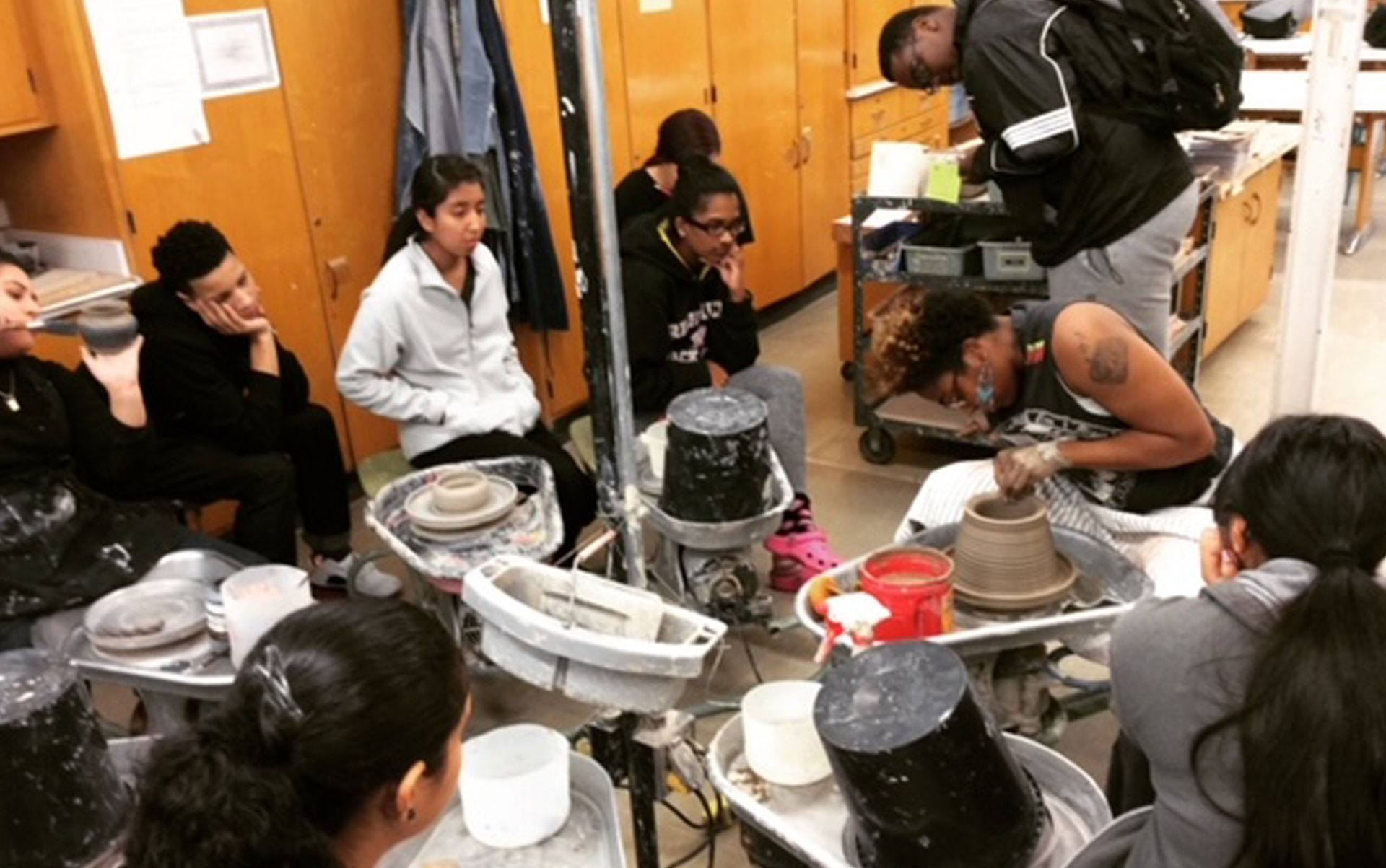 Gabrielle Grier teaching ceramics to a group of young students.
