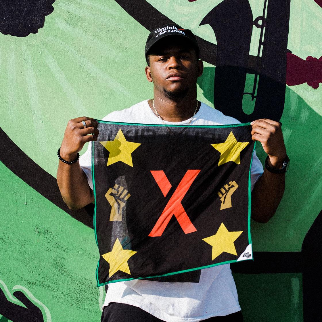 Odis Turner III holding up his design of the JXTA flag bandana