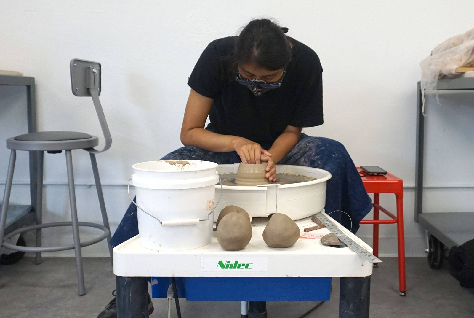 A ceramics lab apprentice spinning a cup on the clay wheel.