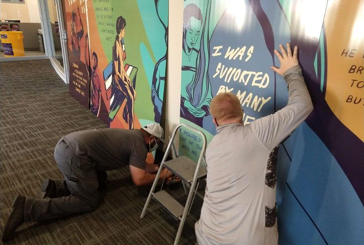 Two people install a colorful mural on an indoor wall.