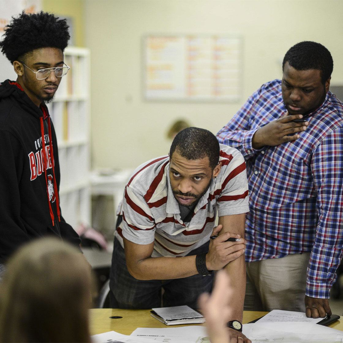 Three Black male-presenting individuals lean over a table, looking at a collaborative project.