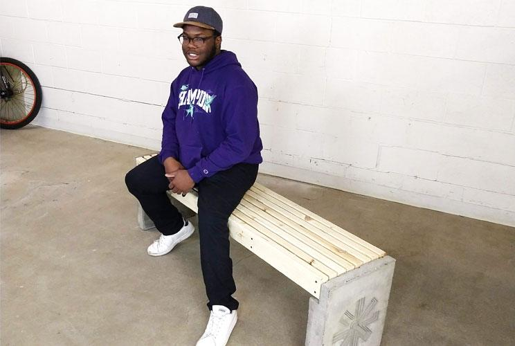 A youth apprentice sitting on a wooden and concrete bench designed by the enviro lab