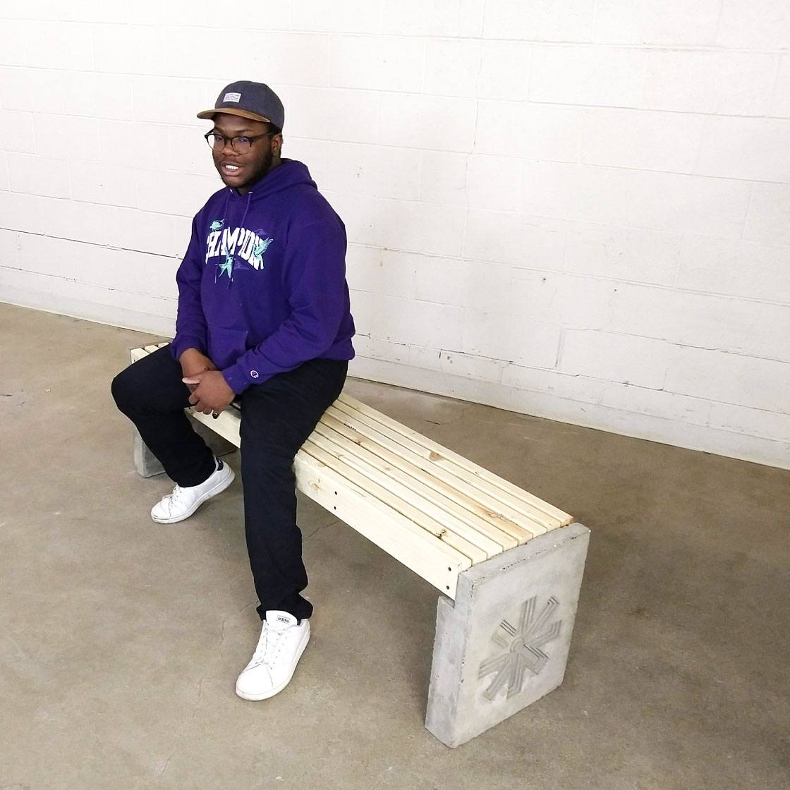 A wooden, concrete, and steel bench designed by Enviro apprentices