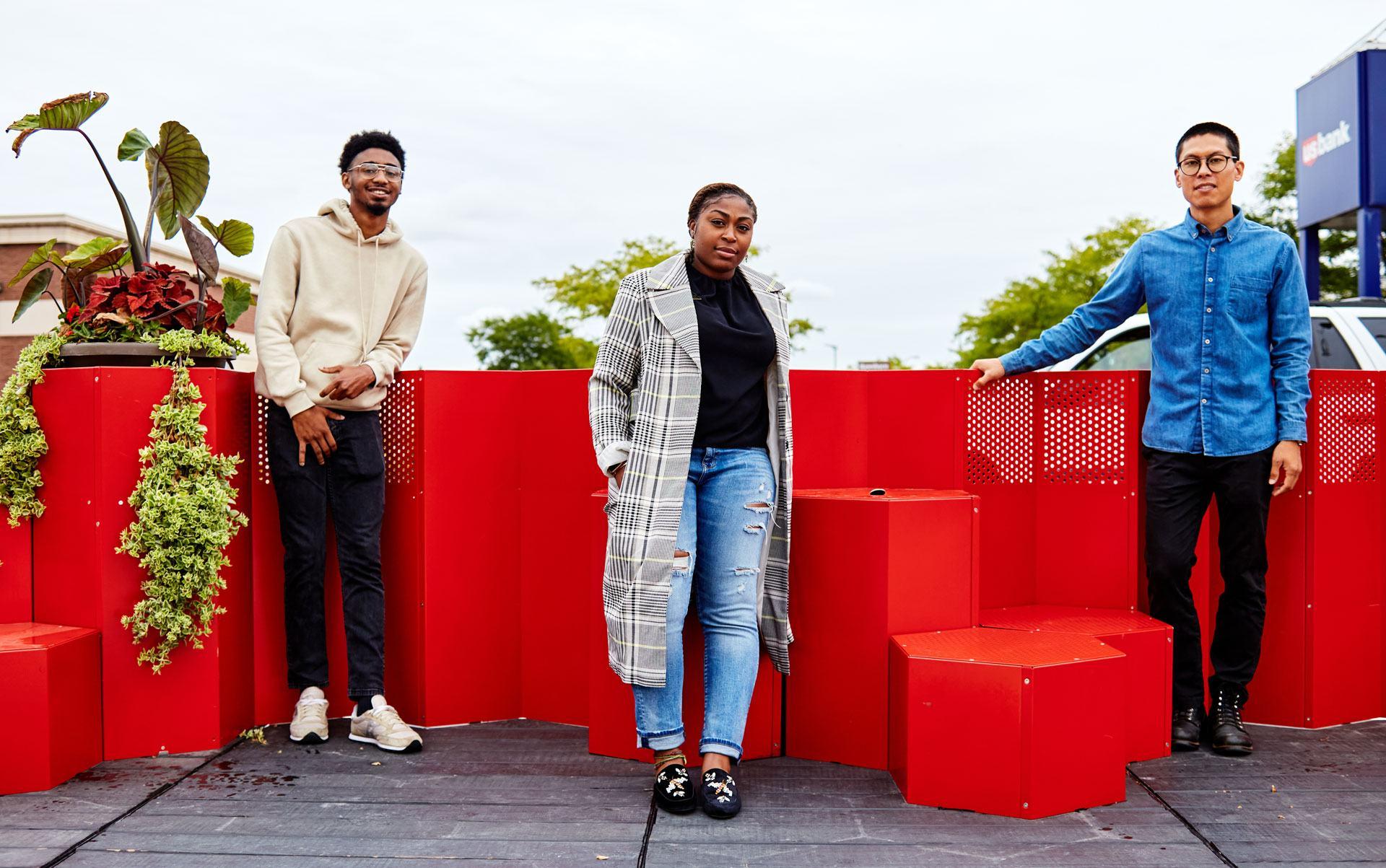 Qadiym Washington, Gabrielle Grier, and Niko Kubota pose in front of the HEXTRA parklet